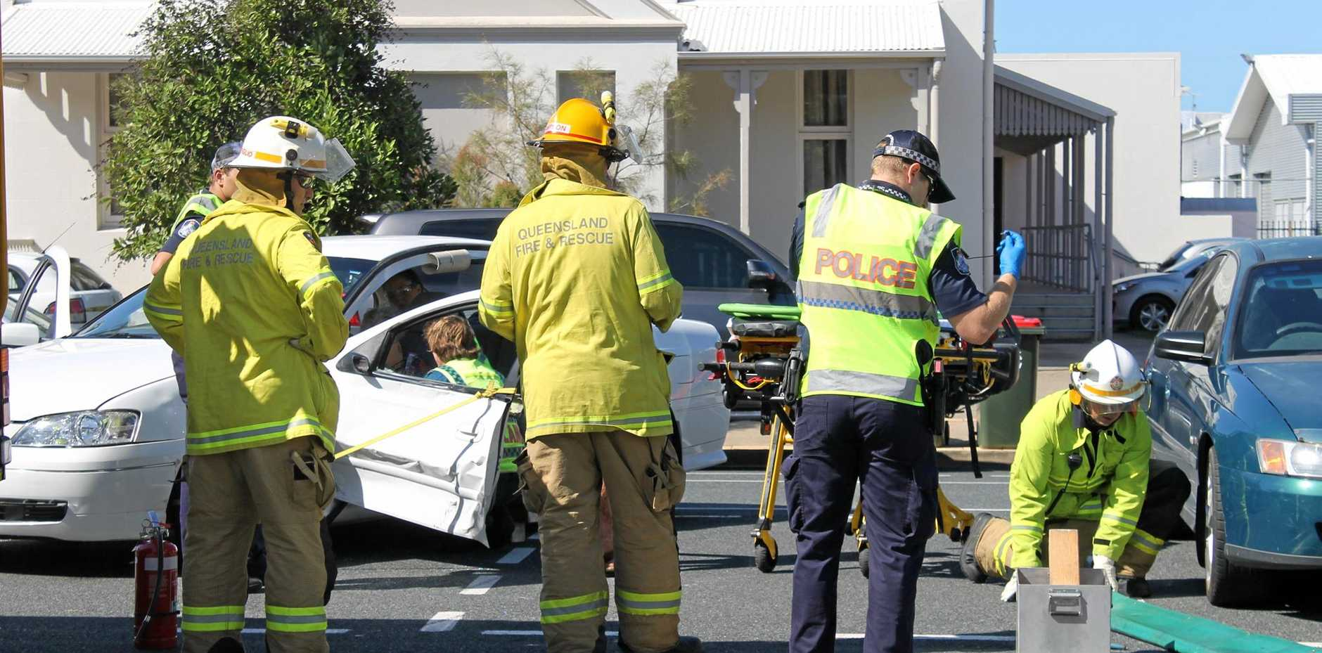 Firefighters work to free an elderly woman after a crash on Gordon St, where it intersects with Macalister St, in Mackay city.