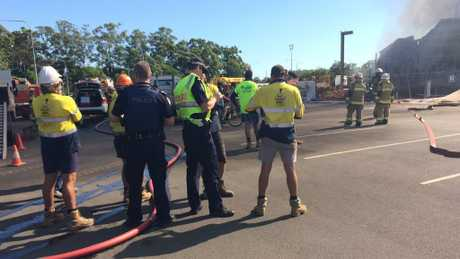 Police talk to workers at the scene of the Maroochydore fire.