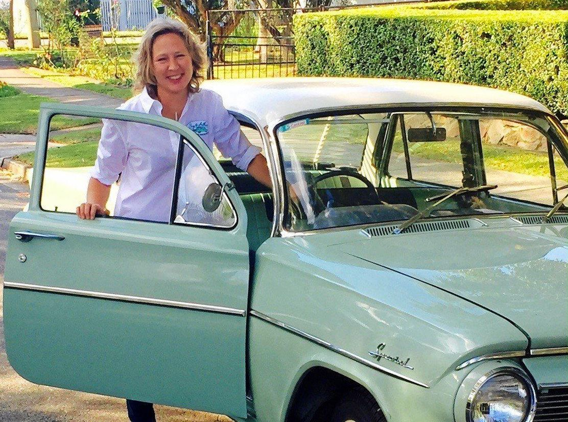 HELPING HAND: Belinda with her beloved vintage Holden that some clients love to drive in.