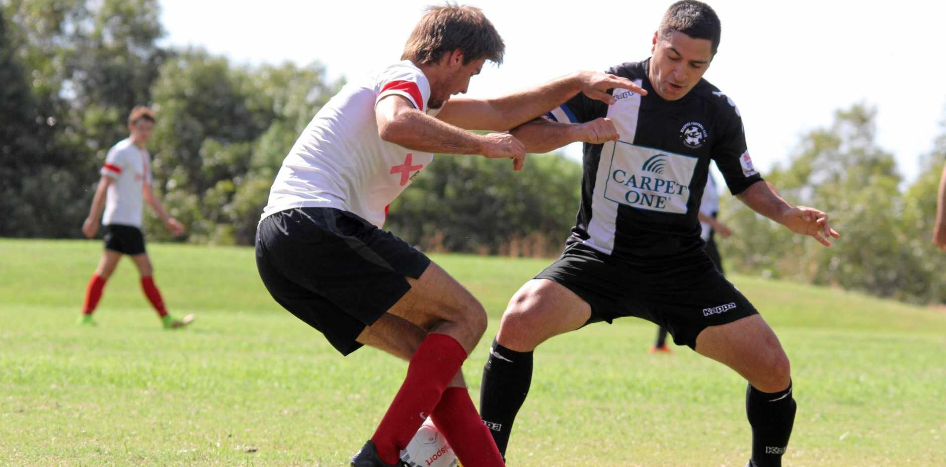 TEAMS JOIN: Magpies' Dean Berry fighting for the ball against Whitsunday FC.