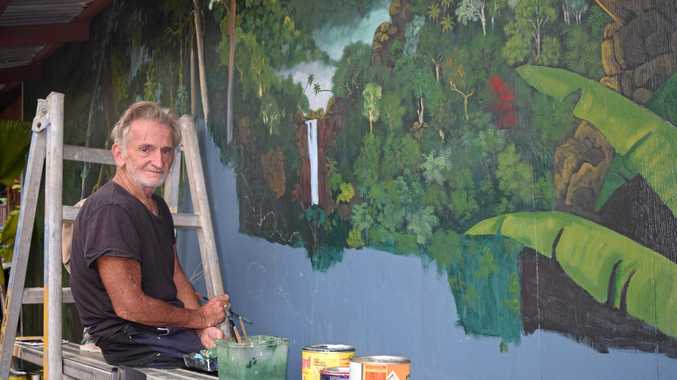 ARTISTIC: Markus Cain working on the mural at Magnums Hotel.