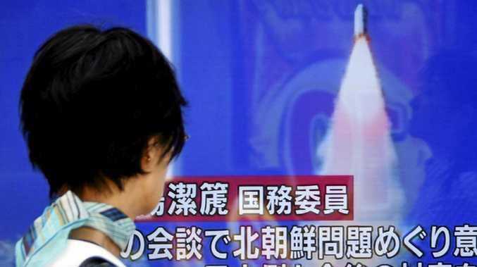 A pedestrian in Tokyo passes a TV screen broadcasting news of North Korea's latest missile launch.