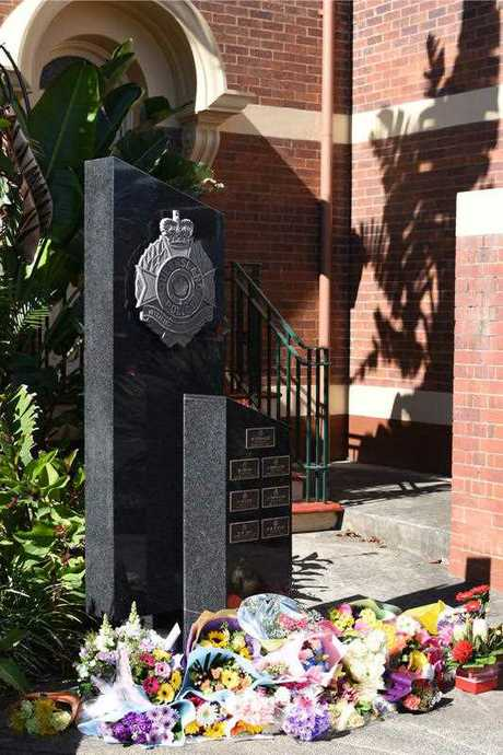 Flowers are laid in memory of a slain police officer at the entrance to the Toowoomba police station in Toowoomba, Queensland
