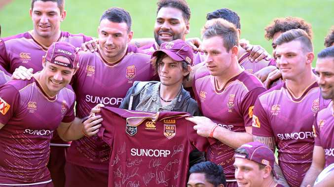 Players pose for a photo with a young fan during the Queensland captain's run at Suncorp Stadium