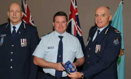 Senior Constable Brett Forte, centre, receives a service medal during his time at Caboolture Police Station.