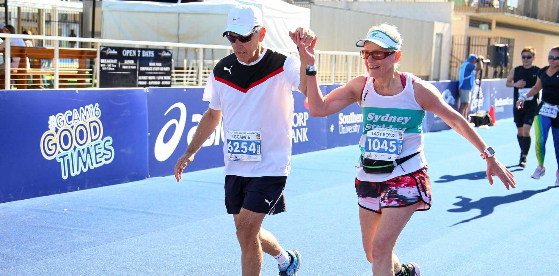 MARATHON SENIOR: Warren Bee and Anne Boyd help each other across the line of the Gold Coast Marathon.