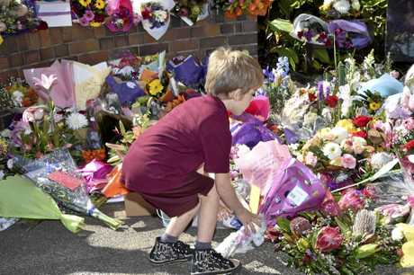 A young boy delivers flowers to the memorial outside Toowoomba Police Station for Brett Forte.
