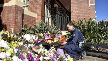 Senior Constable Brett Jacklin lays flowers at the memorial on Friday for Brett Forte.