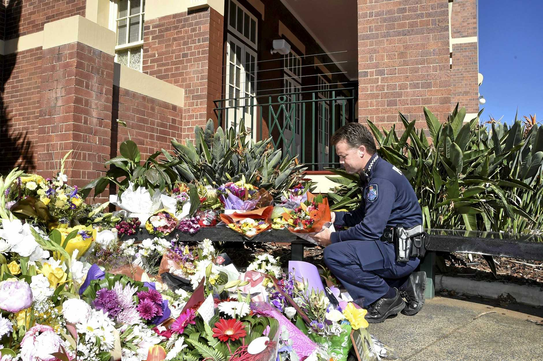 Senior Constable Brett Jacklin lays flowers at the memorial on Friday for Brett Forte.
