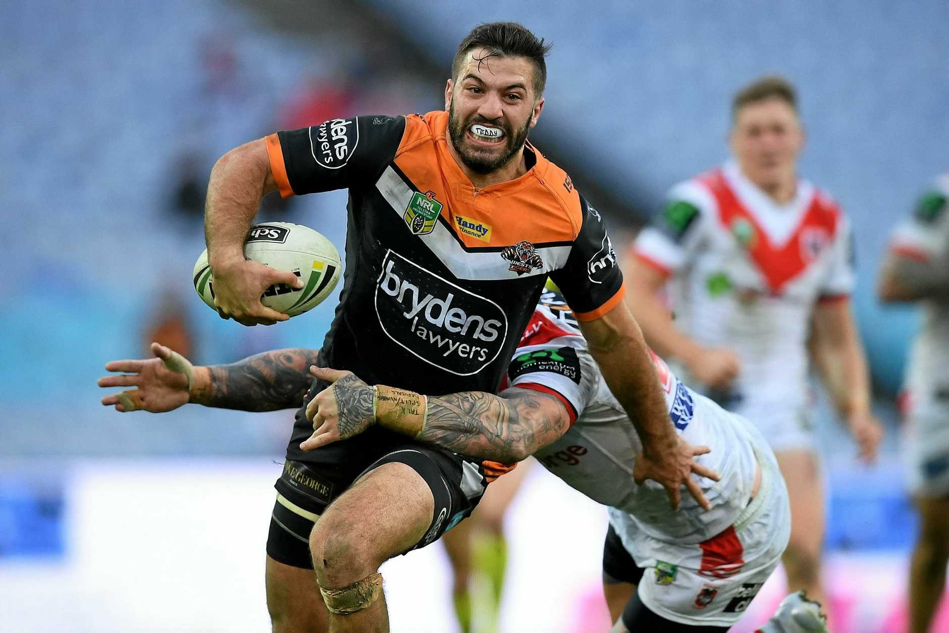 James Tedesco of the Tigers is tackled by Josh Dugan of the Dragons.