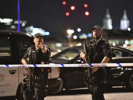 Armed Police officers stand guard on London Bridge in central London. (Dominic Lipinski/PA via AP)