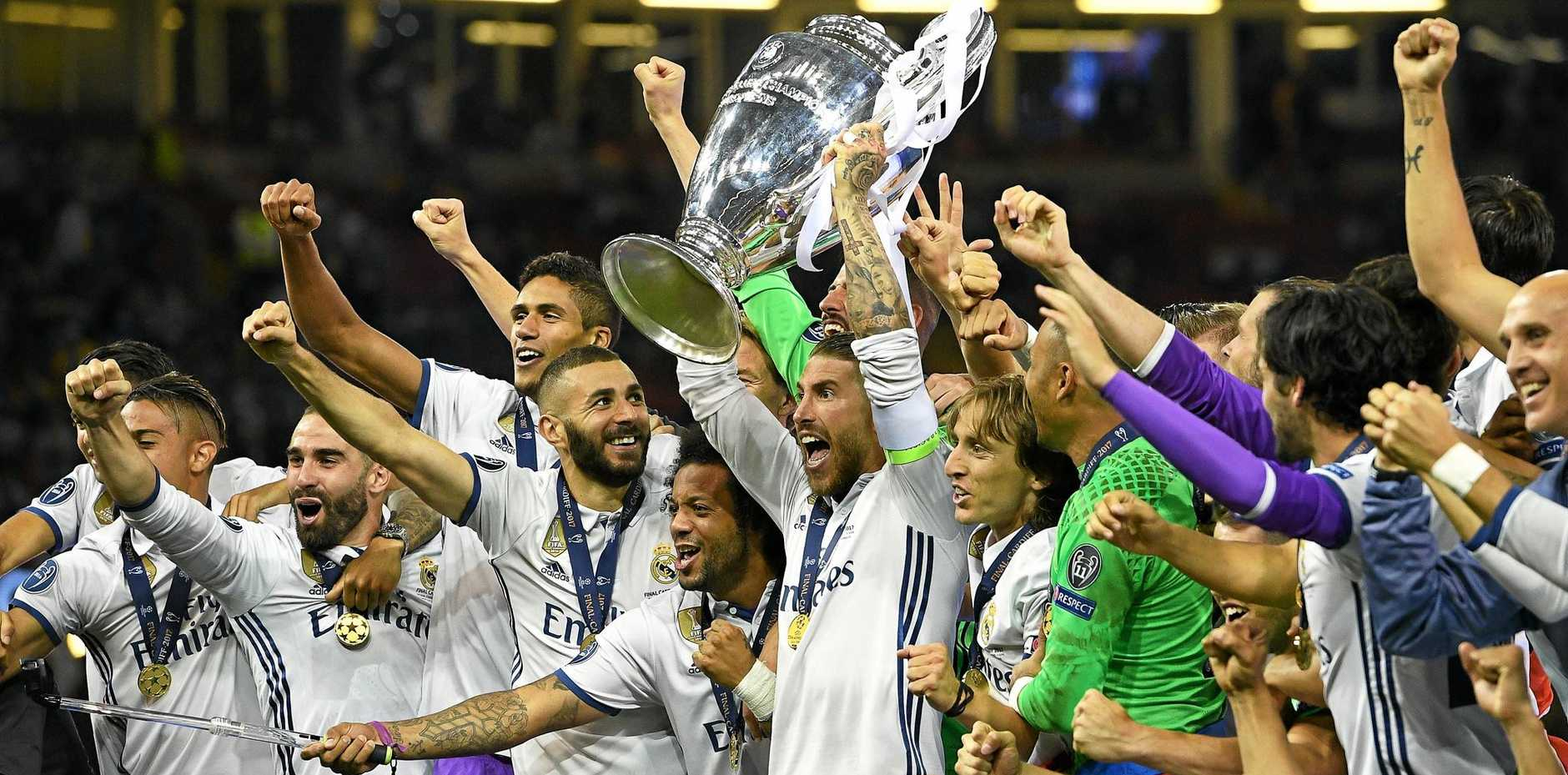 Real Madrid's captain Sergio Ramos (centre) lifts the trophy as his teammates celebrate after the UEFA Champions League final.
