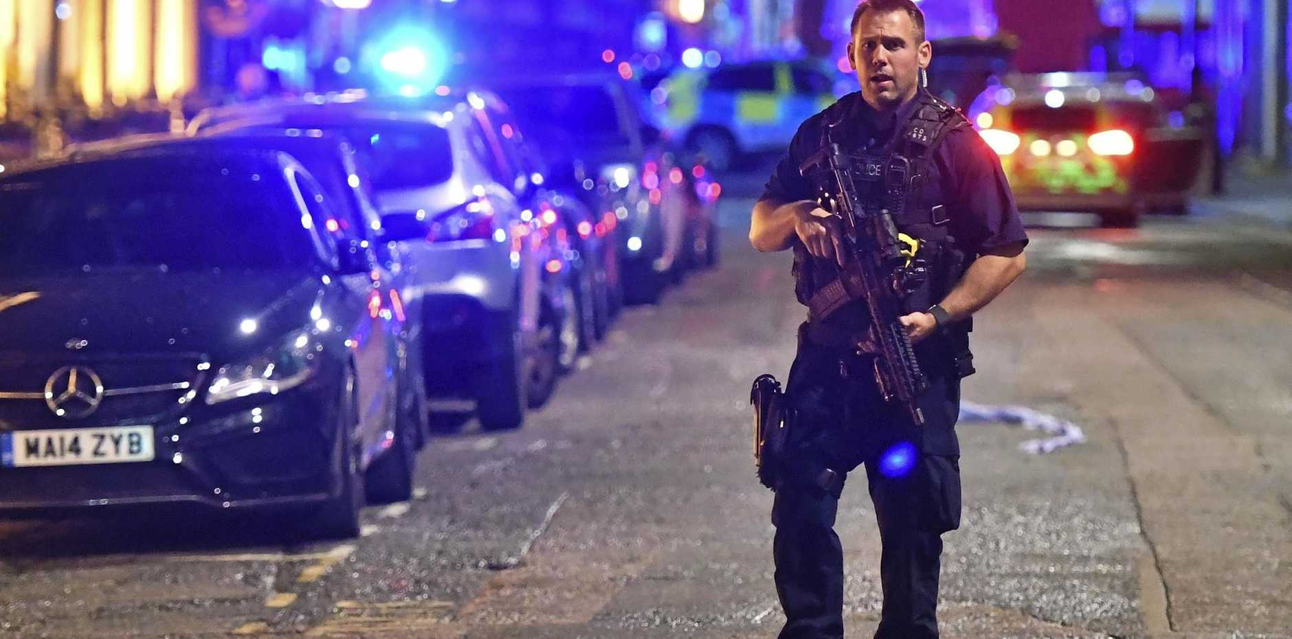 An armed police officer stands on Borough High Street as police deal with an incident on London Bridge on Saturday, June 3.