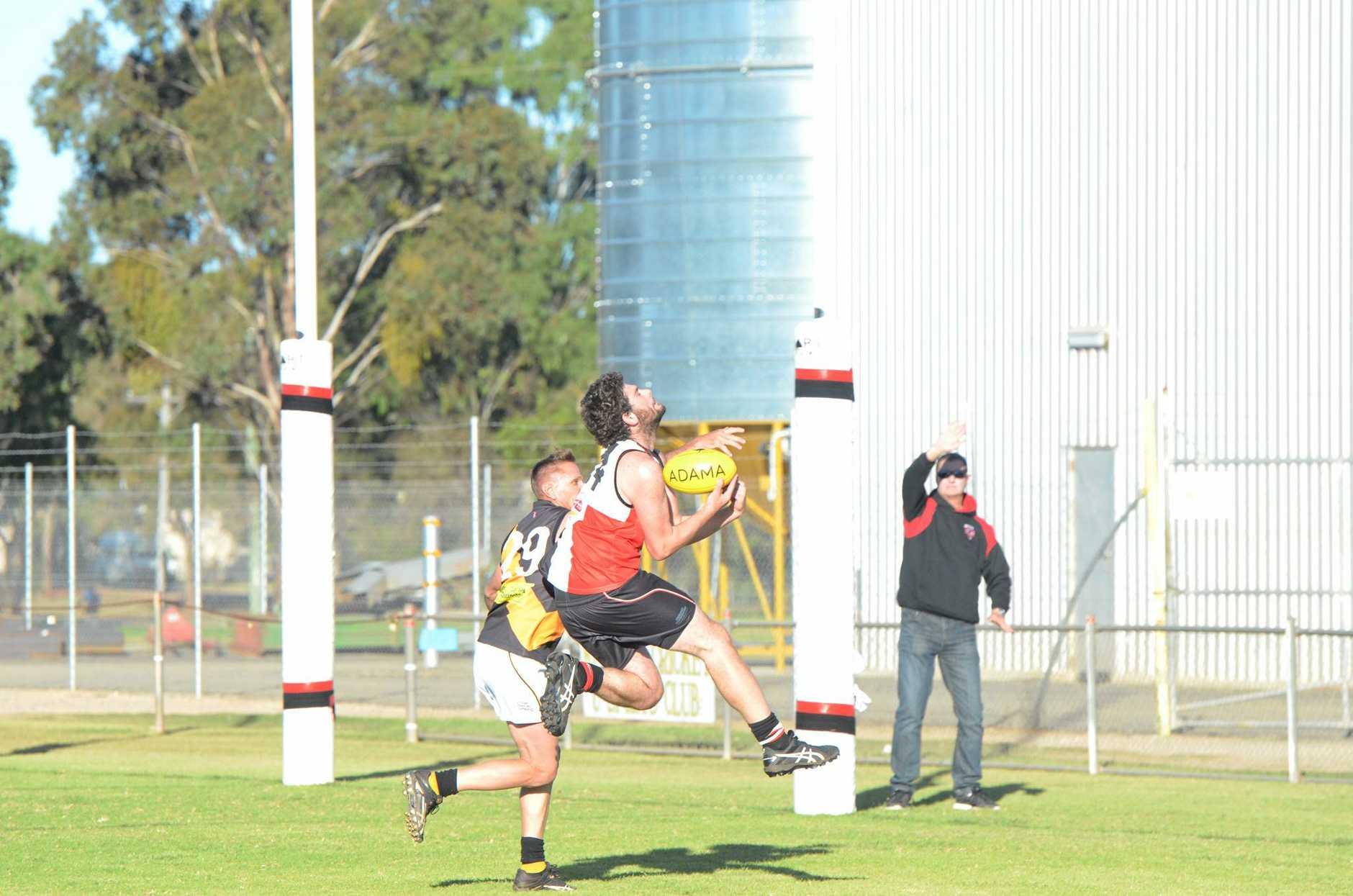 Jordan Pressnell takes a mark running back toward goal.