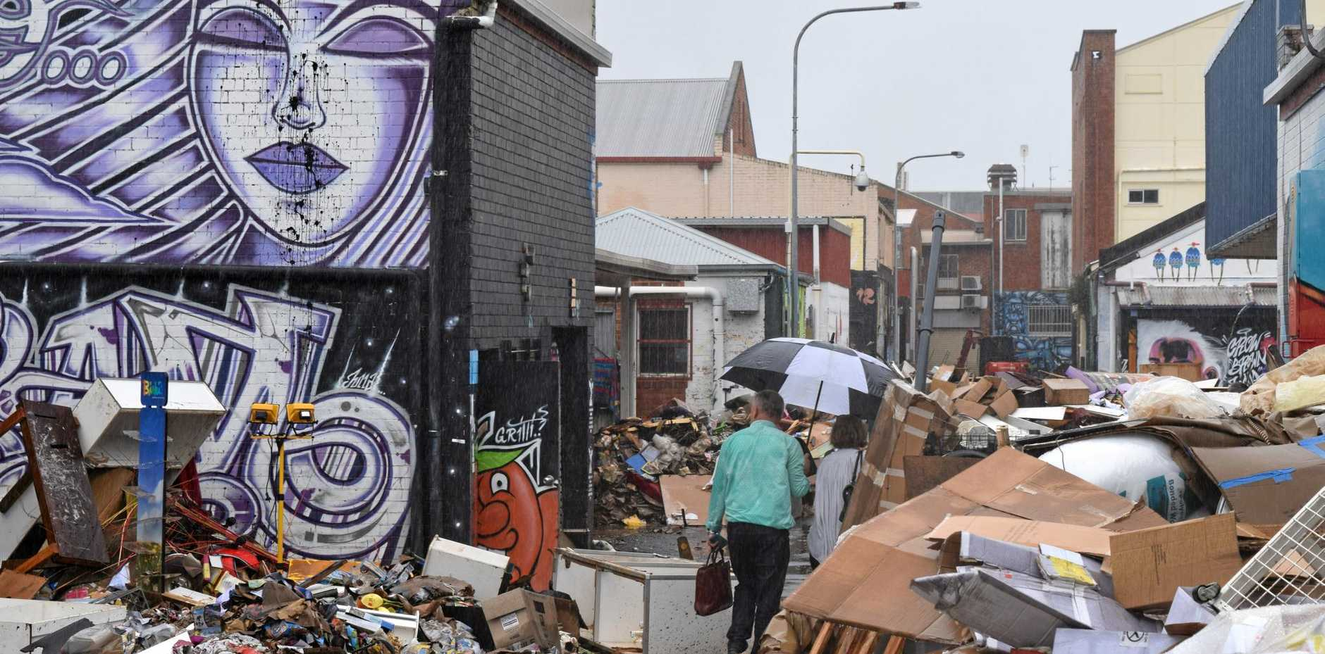 Piles of ruined goods and rubbish fill back streets of Lismore's CBD.