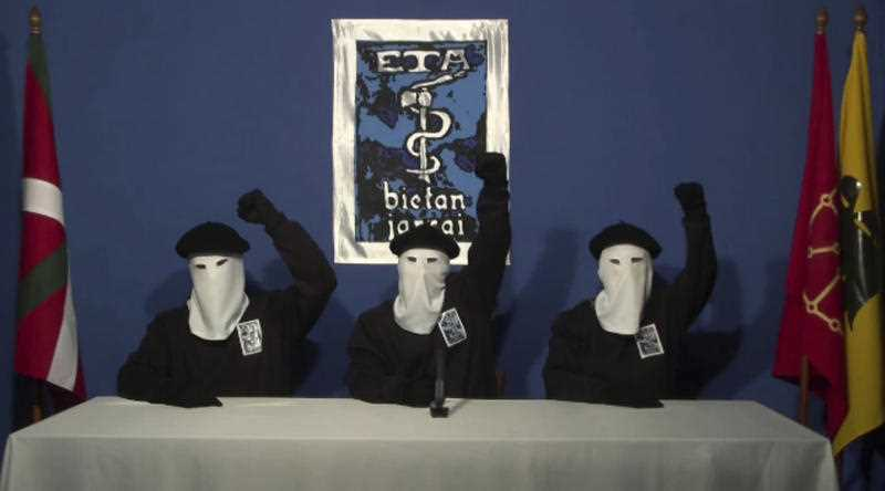Masked members of the Basque separatist group ETA raise their fists in unison following a news conference at an unknown location.