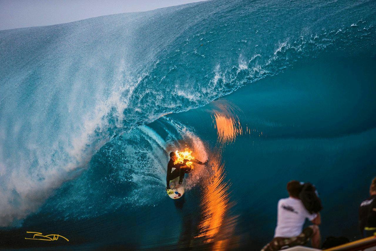 Tim Bonython shooting Hawaii's Jamie O'brien, who is literally on fire at Teahupo, Tahiti.