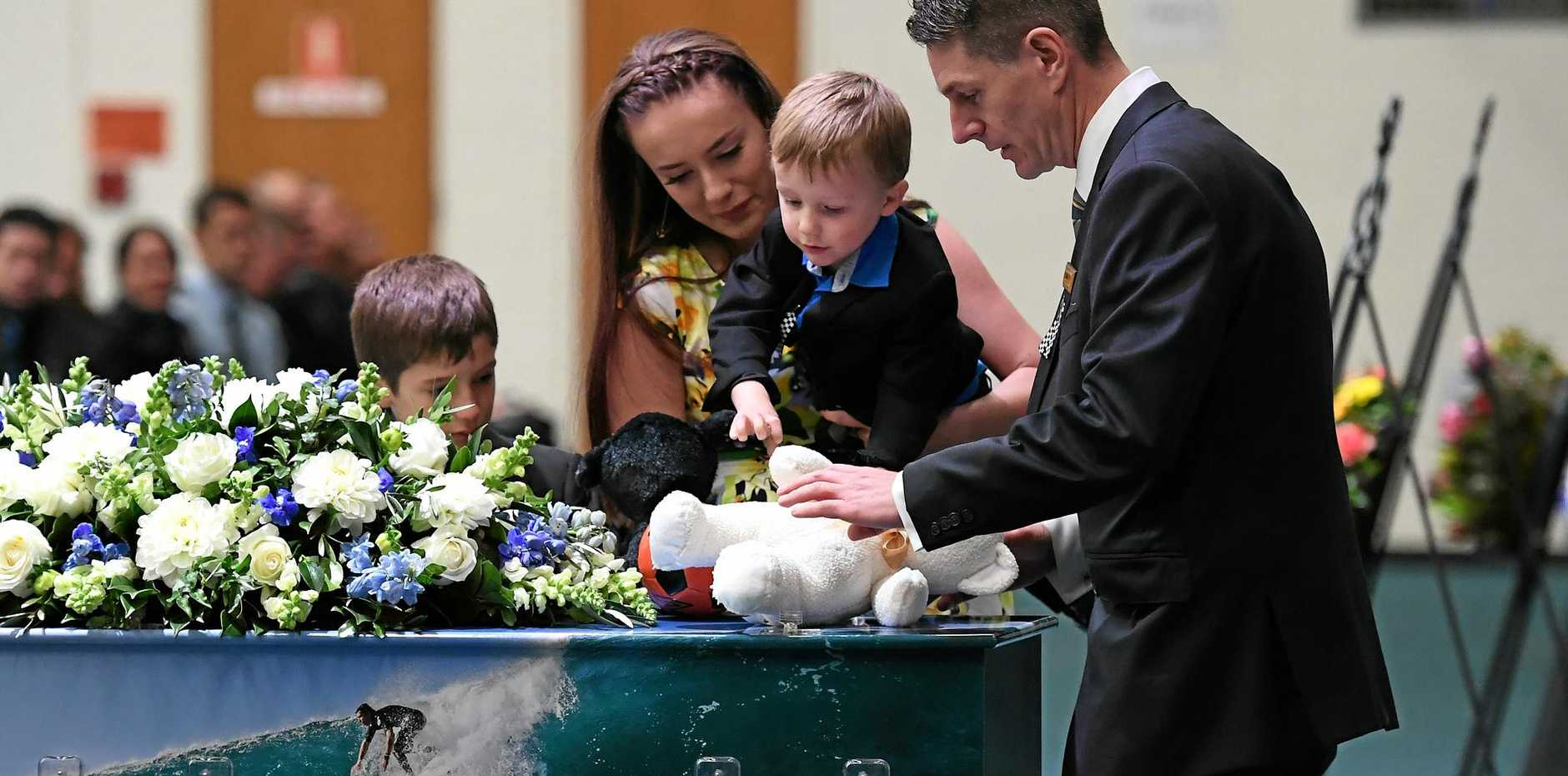 Senior Constable Brett Forte's children (2nd right to left) Sam, Emma and Brodie place a teddy bear and other items on his casket during his funeral service in Toowoomba. (AAP Image/Dan Peled)