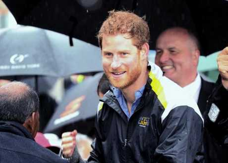 Prince Harry is all smiles despite the bad weather.