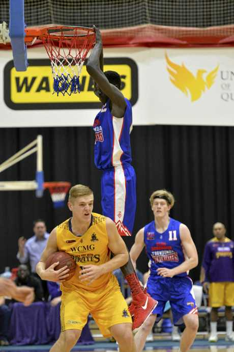 Paul Aleer of Toowoomba Mountaineers hangs from the basket over Tanner McGrew of South-West Metro Pirates in QBL men's basketball at USQ's Clive Berghofer Recreation Centre.