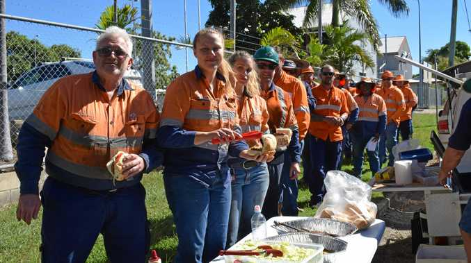 STANDING FIRM: Workers at Rockhampton's Aurizon workshop line up for a burger provided by the unions. A rally is being planned for next Monday.