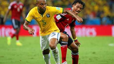 Fernandinho (left) of Brazil gets past Juan Cuadrado of Colombia.