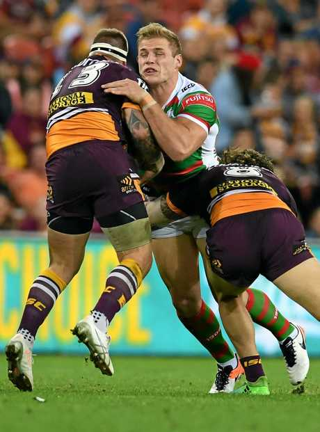 Tom Burgess of the South Sydney Rabbitohs (centre) is tackled the Brisbane Broncos.