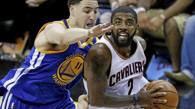 Cleveland Cavaliers guard Kyrie Irving drives past the Golden State Warriors' Klay Thompson.