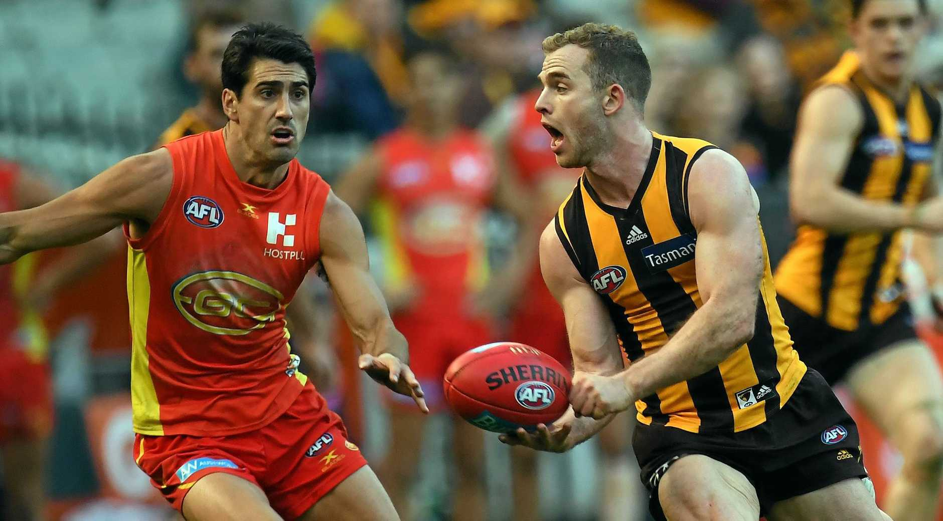 Tom Mitchell of the Hawks and Matt Rosa of the Suns (left) contest during the Round 12 AFL match between the Hawthorn Hawks and the Gold Coast Suns at the MCG in Melbourne, Saturday, June 10, 2017. (AAP Image/Julian Smith) NO ARCHIVING, EDITORIAL USE ONLY
