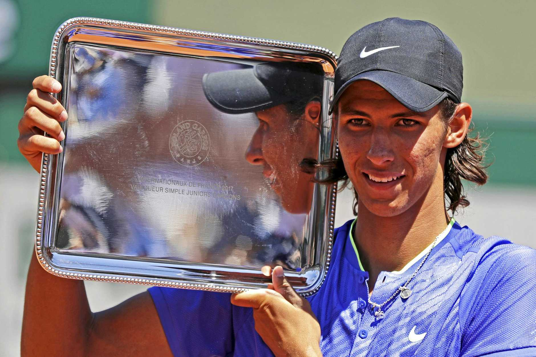 Australia's Alexei Popyrin hold the trophy after winning the boys' final of the French Open.