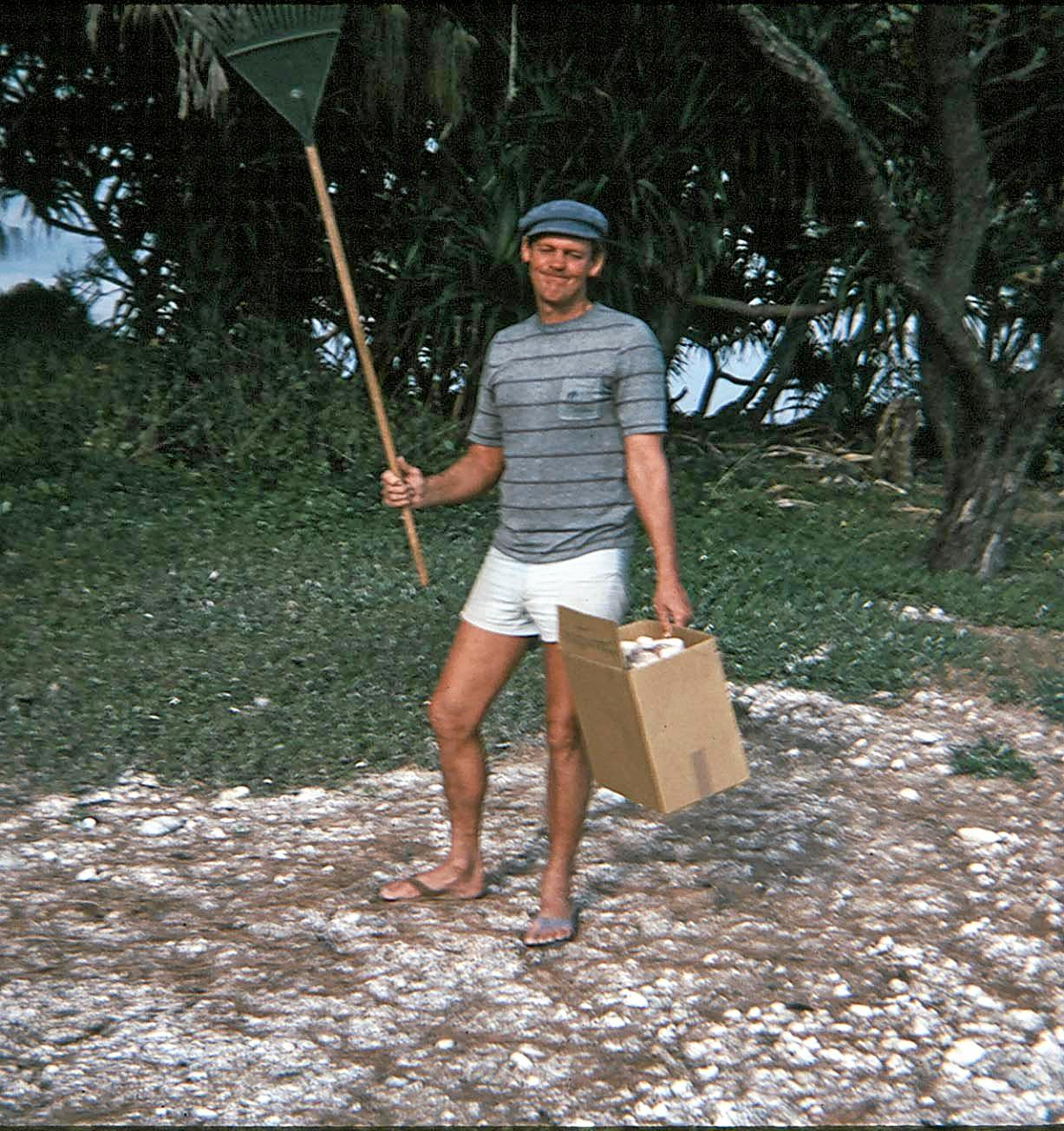 Peter Troy wears odd thongs found on Old Woman Island as he rakes pandanus leaves and collects rubbish, some time in the 1980s.