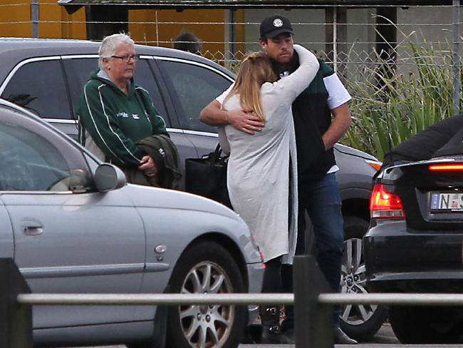 A man and woman hug at the scene.