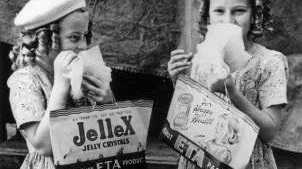 Historic photos of two girls getting early samples of show bags in the 1940s.