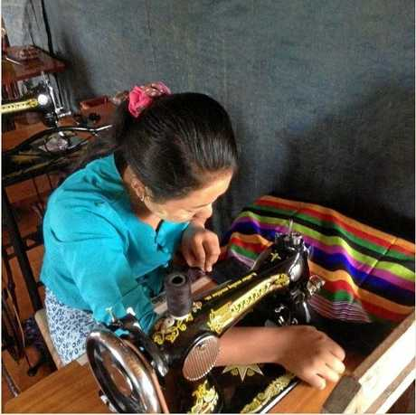 A Myanmarese woman makes her first item of clothing on a donated sewing machine.