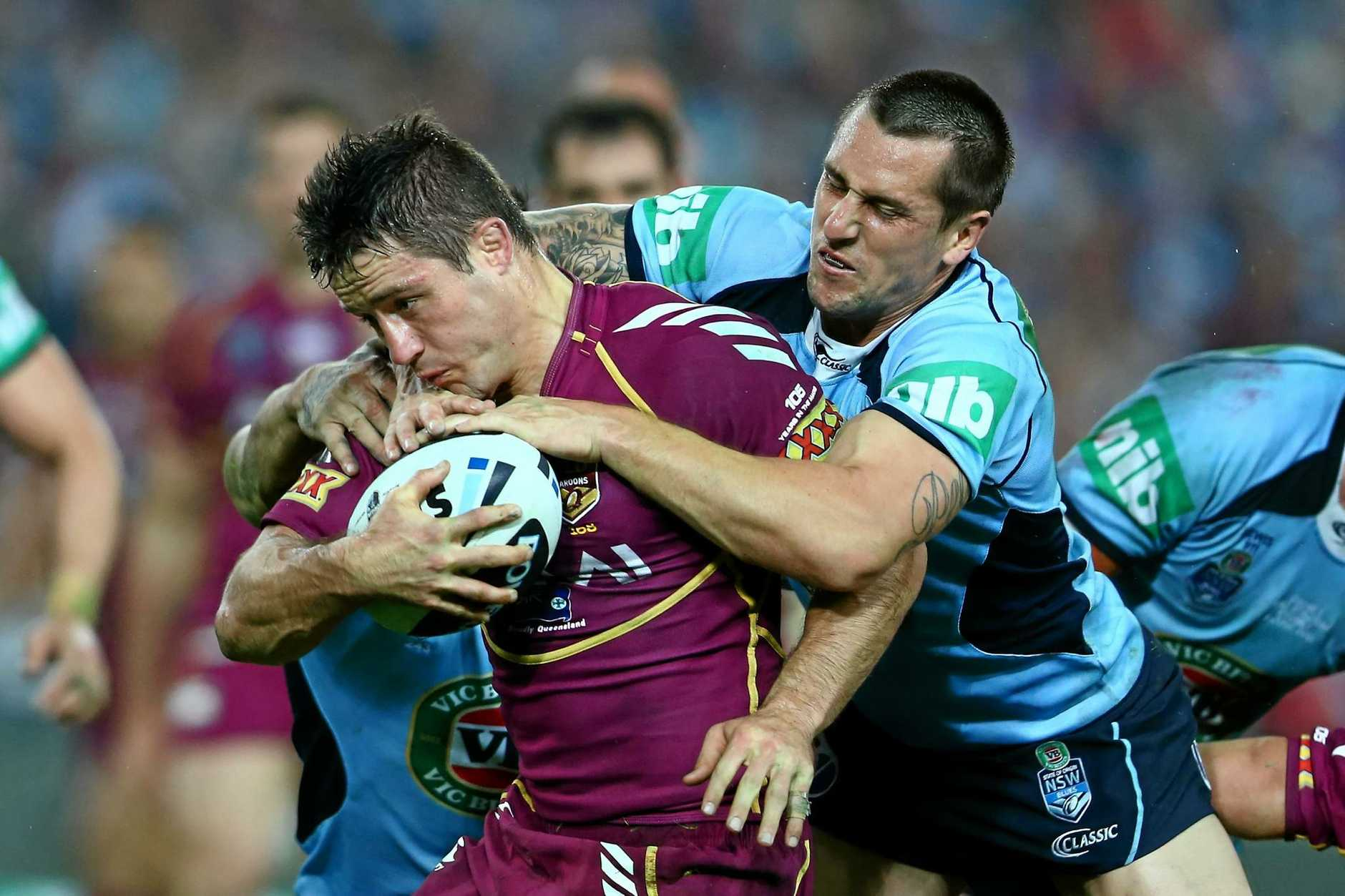 Cooper Cronk is tackled by Mitchell Pearce during game one