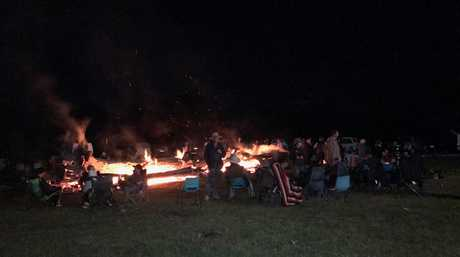 People gather around the fire and listen to the live music.