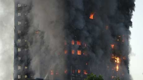 Smoke and flames rise from building on fire in London, Wednesday, June 14, 2017. Metropolitan Police in London say they're continuing to evacuate people from a massive apartment fire in west London. The fire has been burning for more than three hours and stretches from the second to the 27th floor of the building.