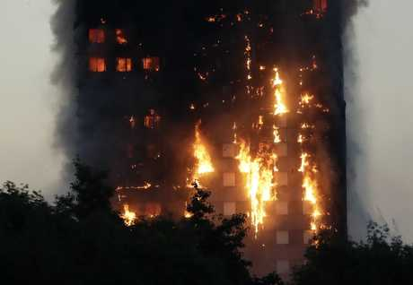 Smoke and flames rise from a building on fire in London, Wednesday, June 14, 2017. Metropolitan Police in London say they're continuing to evacuate people from a massive apartment fire in west London.
