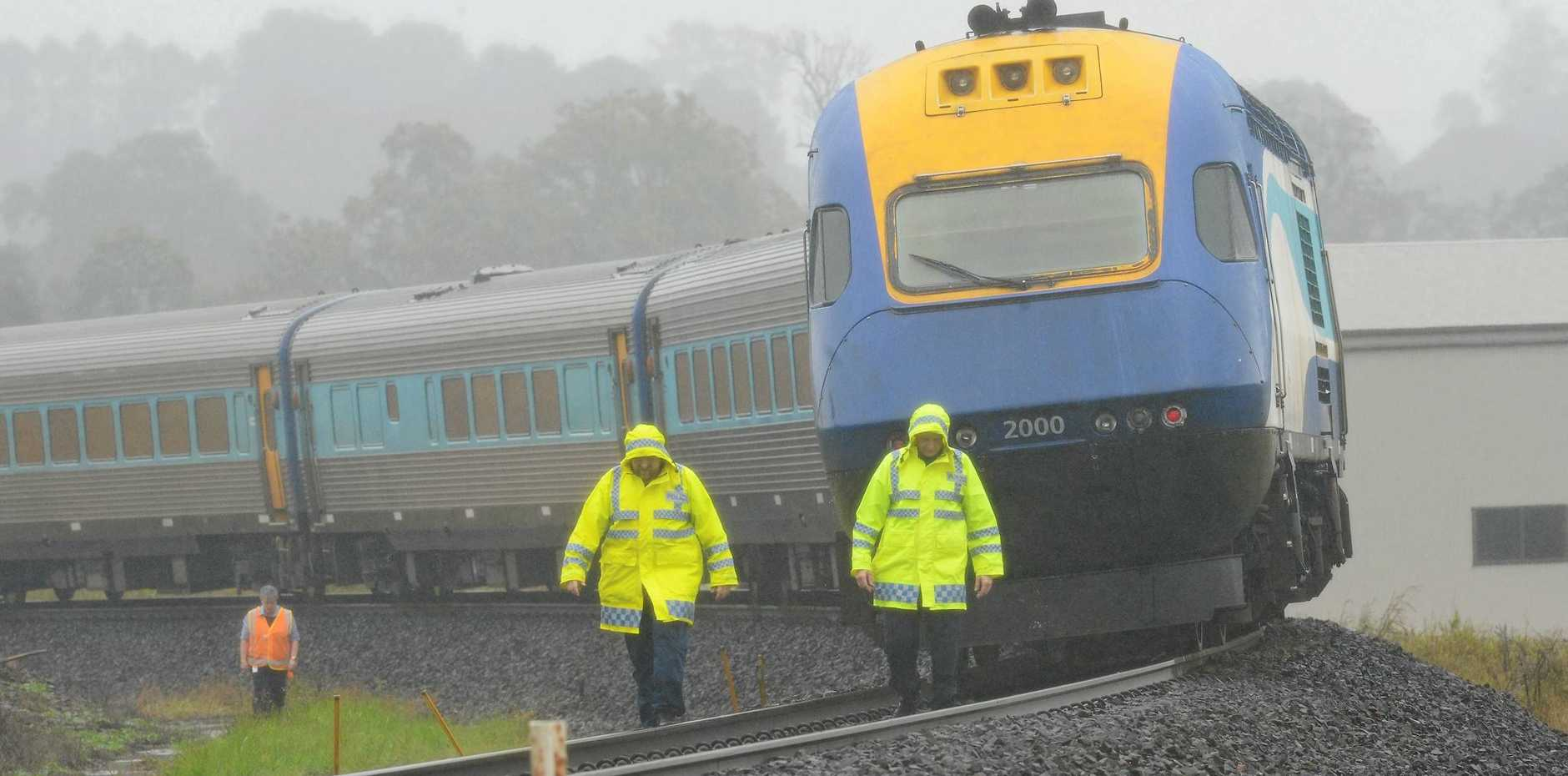SOMBRE: Police at the scene where a car was hit by a train at a road crossing in Kyogle yesterday.