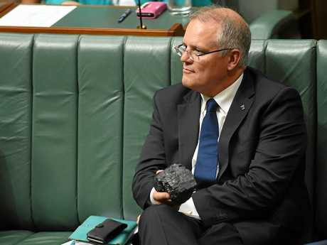 Australia's Treasurer Scott Morrison looks at a piece of coal during House of Representatives Question Time at Parliament House in Canberra, Thursday, Feb. 9, 2017. (AAP Image/Lukas Coch) NO ARCHIVING