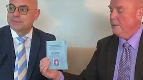 John McLeod hands Schapelle Corby's parole book over to Glenn Thexton.