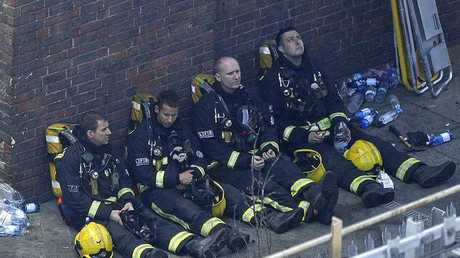 Firefighters rest as they take a break in battling a massive fire that raged in a high-rise apartment building in London, Wednesday, June 14, 2017.