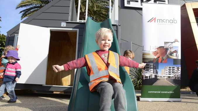 SLIDE AND SMILE: Toowoomba boy Will Aulsebrook tries out the winning cubby house by McNab Construction, which beat designs by Hutchinson Builders and FKG Group. All buildings will be auctioned off in August.