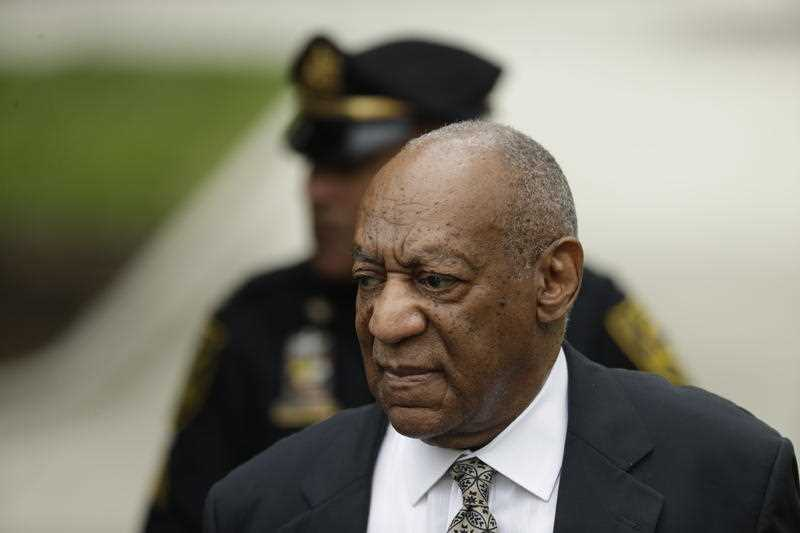 Bill Cosby, left, exits the courtroom during jury deliberations in his sexual assault trial.