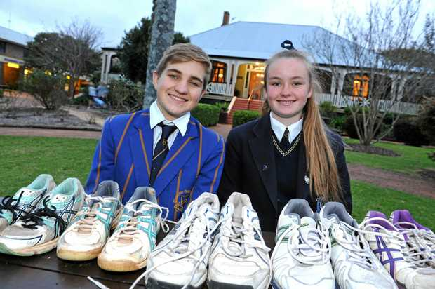MANY SHOES: Toowoomba Grammar School's Adrian Irwin and Fairholme College's Libby Stumer with shoes collected for children in Zambia.