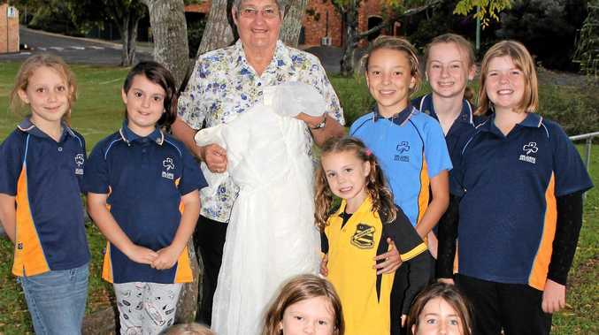 Josie Fry from the Sunshine Wanderers Trefoil Guild shows her debutante dress to the Nambour Girl Guides girls.