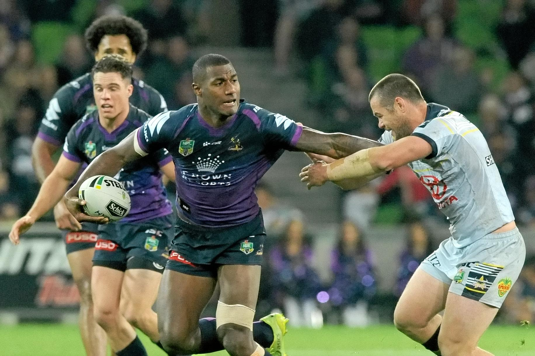 Suliasi Vunivalu of the Storm beats a tackle by Shaun Fensom of the Cowboys.