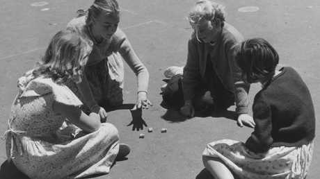 Four girls playing Jacks in Melbourne in 1954.Source:Supplied