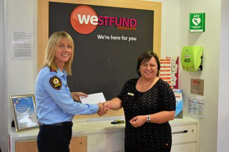 Local Controller Mackay SES Selina Neill accepts the donation from Westfund Regional Manager Elsie Van Staden.