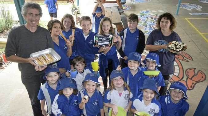 HEALTHY CHOICES: Cowper Public School canteen co-ordinators Ian Versace (left) and Sherrie Piper (right) with students and healthy tuck shop options.